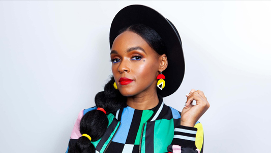 Singer Janelle Monáe wearing a black hat and a colourful top