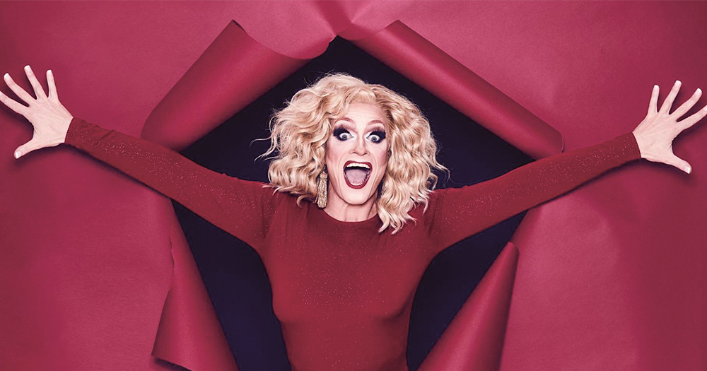 A drag queen jumping out of Christmas wrapping to celebrate Winter Pride