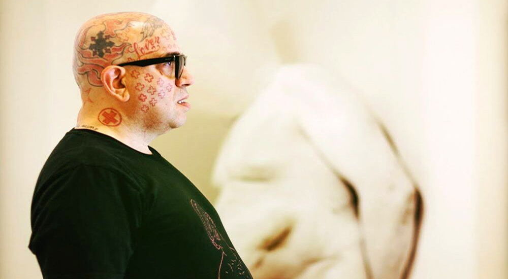 Artist Franko B, a heavily tattooed bald man, stands sideways to the camera. He is standing opposite a white sculpted figure roughly the same shape as him.