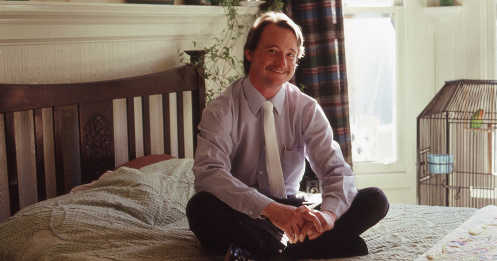 A smiling man sits crosslegged on a bed
