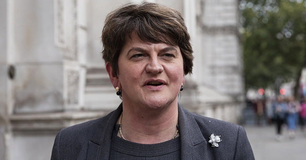 Arlene Foster in a jacket standing outside a government building