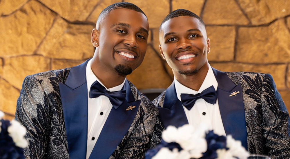 The picture shows two grooms on their wedding day. They are wearing flowery blue suits and there is a yellow background. They look really happy.