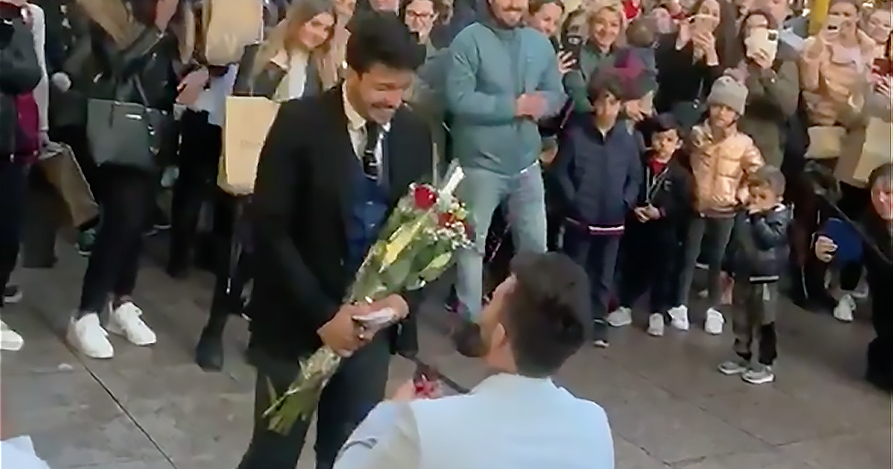 A man on his knees proposing to his partner who is holding roses in this gay couple proposal video