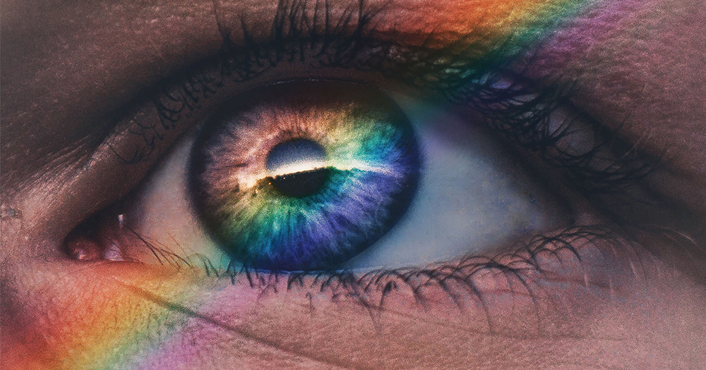 A close up of an eye with a rainbow light reflected in it