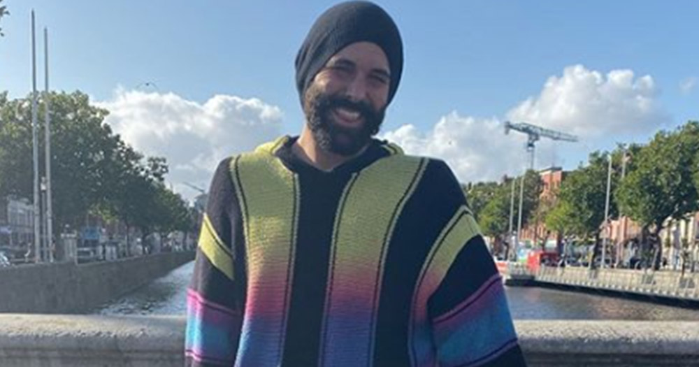 Jonathan Van Ness on O'Connell Bridge wearing a multi coloured gradient hoodie.