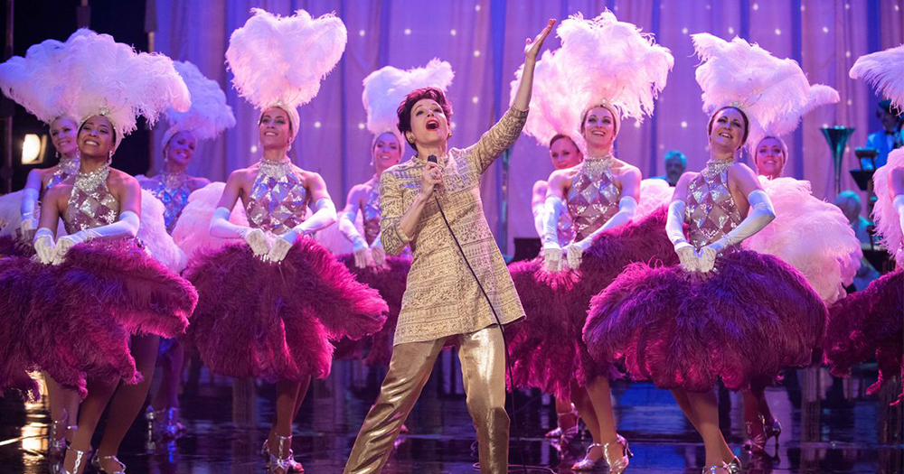 In a scene from the film Judy Garland in a shiny suit sings on stage in front of a chorus line of showgirls