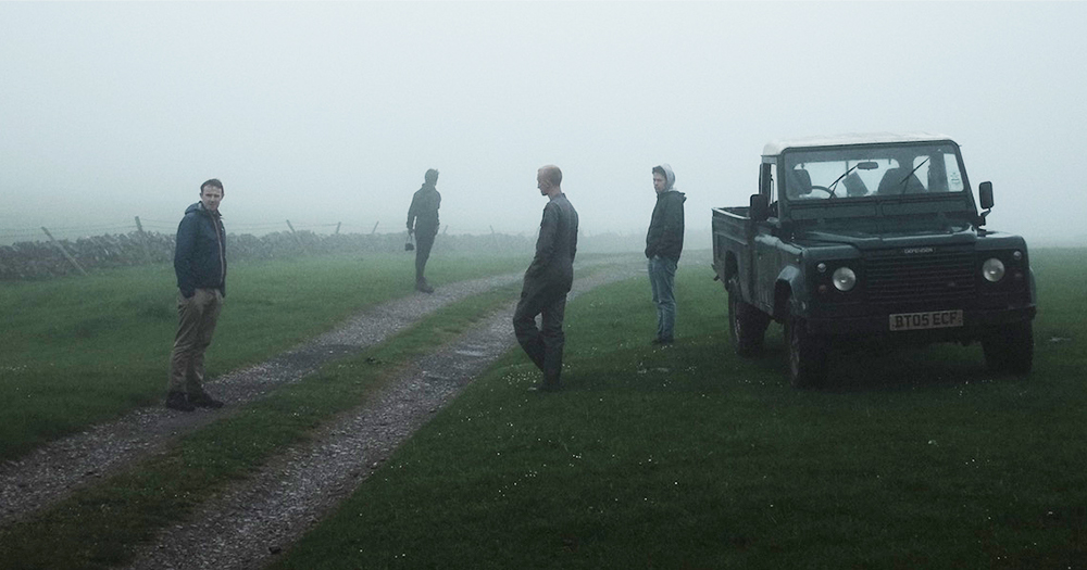 Four men stand spread out in a misty rural area, a jeep in the background