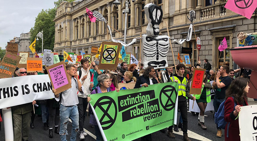 Image of protestors walking down a street by the Dail holding banners and signs. At the front is agreen abnner that says Extinction Rebellion.