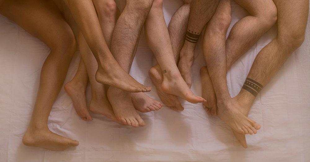 A tangle of naked legs in a gay orgy