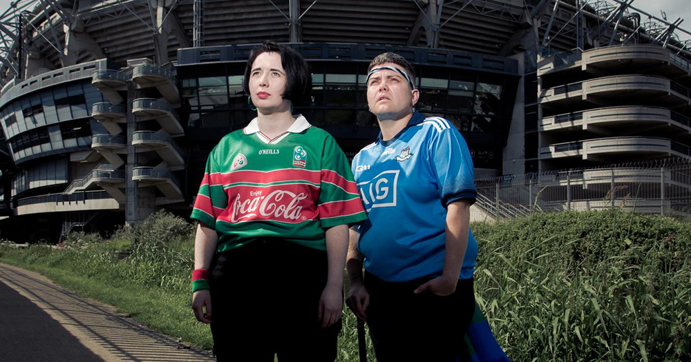 Outburst Queer Arts Festival show GAA MAAD depicting two women in GAA tops standing outside a sports stadium