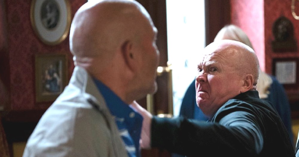 Phil Mitchell in the pub preparing to punch another man