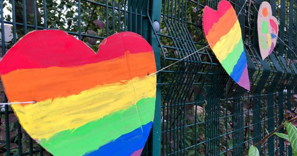 Cardboard rainbow hearts made by pupils hanging on a school railing