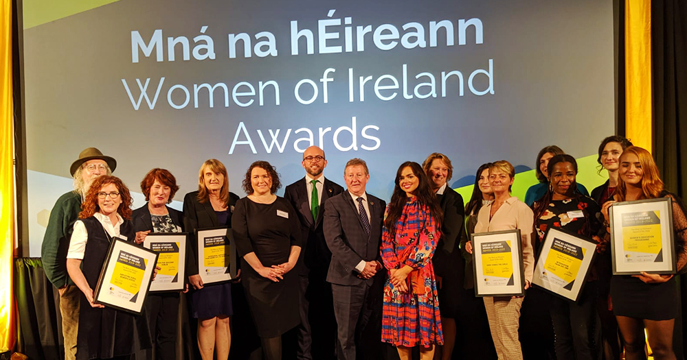 The stage at the Mná na hÉireann awards with a group of people holding awards alongside the hosts