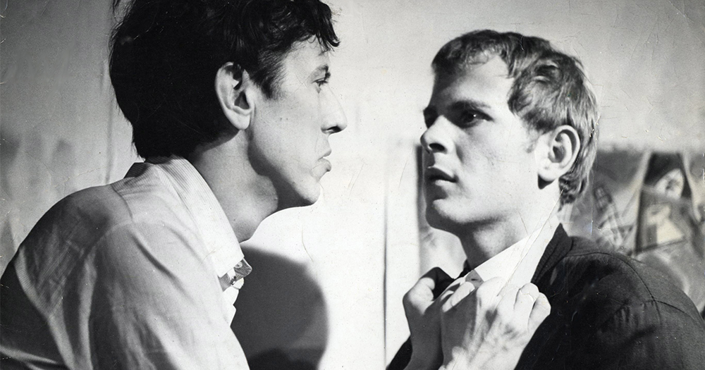 A scene from The Haunted Host consisting of a black and white photo of two men, one gripping the other's collar