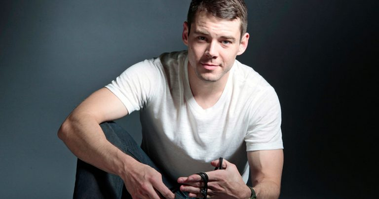 Brian J Smith sitting on the ground with rope around his fingers.