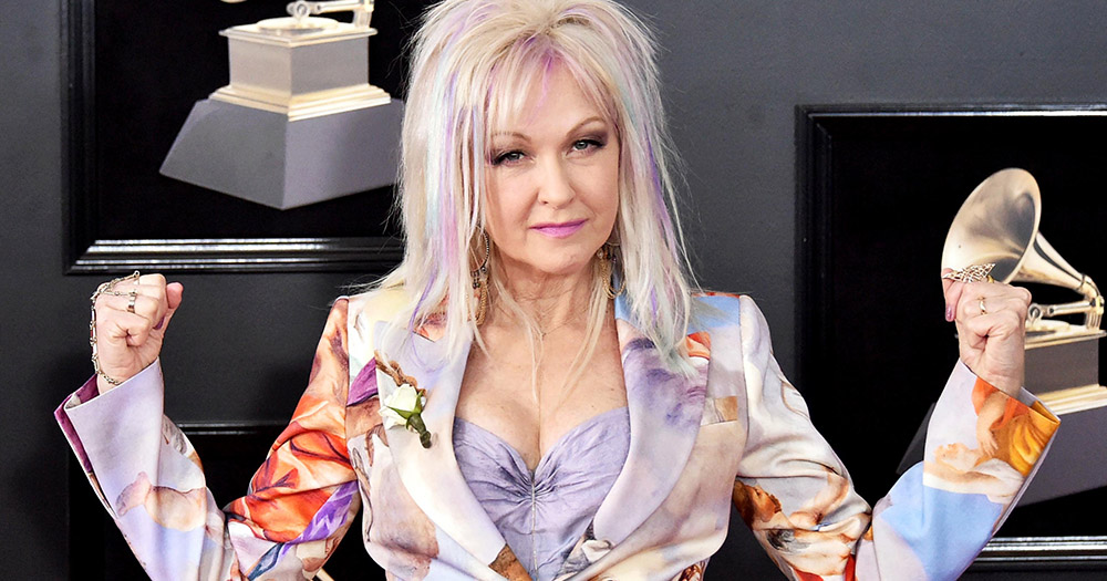 Cyndi Lauper wearing a pastel suit with tiny cupids on it and flexing at the Grammys 2018.