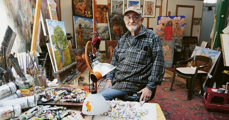 Artist Delmas Howe sitting in his studio, surrounded by his paintings