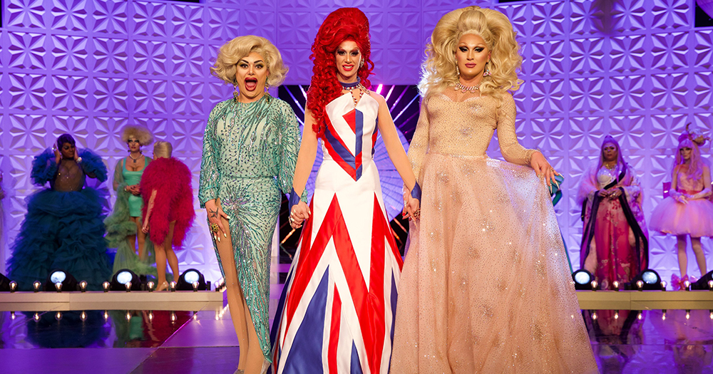 The Drag Race UK final three drag queens stand on the runway, holding hands