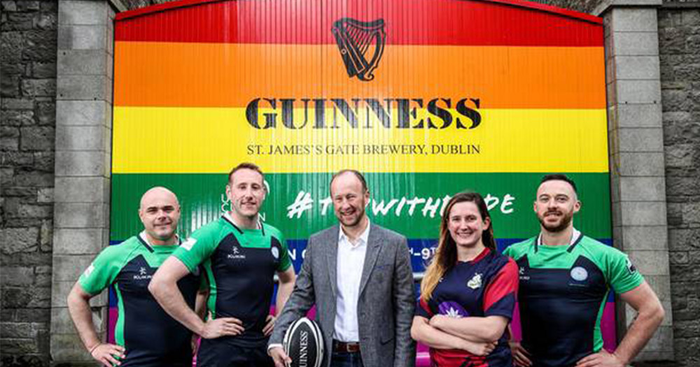 A group of rugby players, dressed in both jerseys and suits, stand in front of the Guinness brewery gates which are painted with a rainbow.