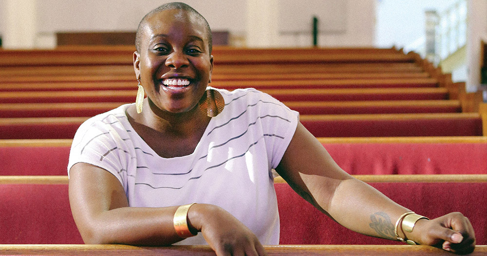 Reverend Kyndra Frazier sitting in the pews and smiling. She is one of the female pastors who are making religion a safe space for queer people.