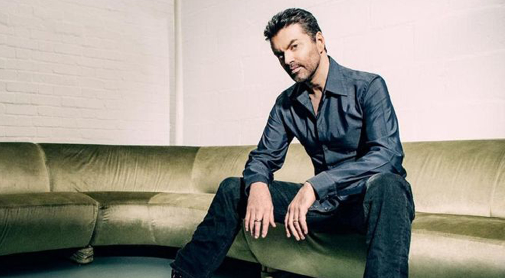 George Michael sits on a sofa