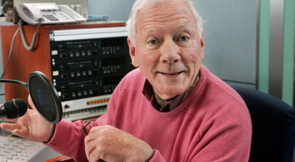 Gay Byrne smiling in a radio recording studio.