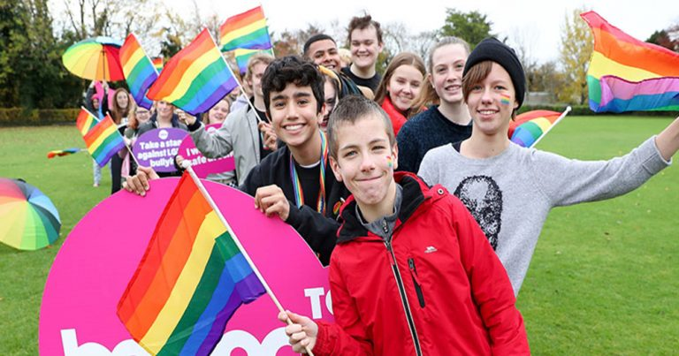School children wearing rainbow face paint and holding rainbow flags in support of BeLonG To's Stand Up Awareness week