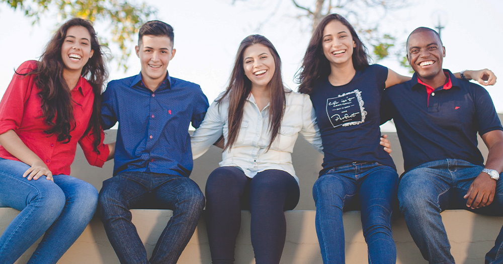 A group of five youth workers posing together smiling with their arms around each other