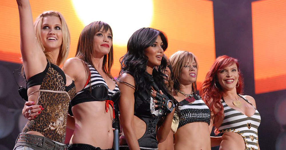 The Pussycat Dolls smiling at a crowd of fans after a concert.
