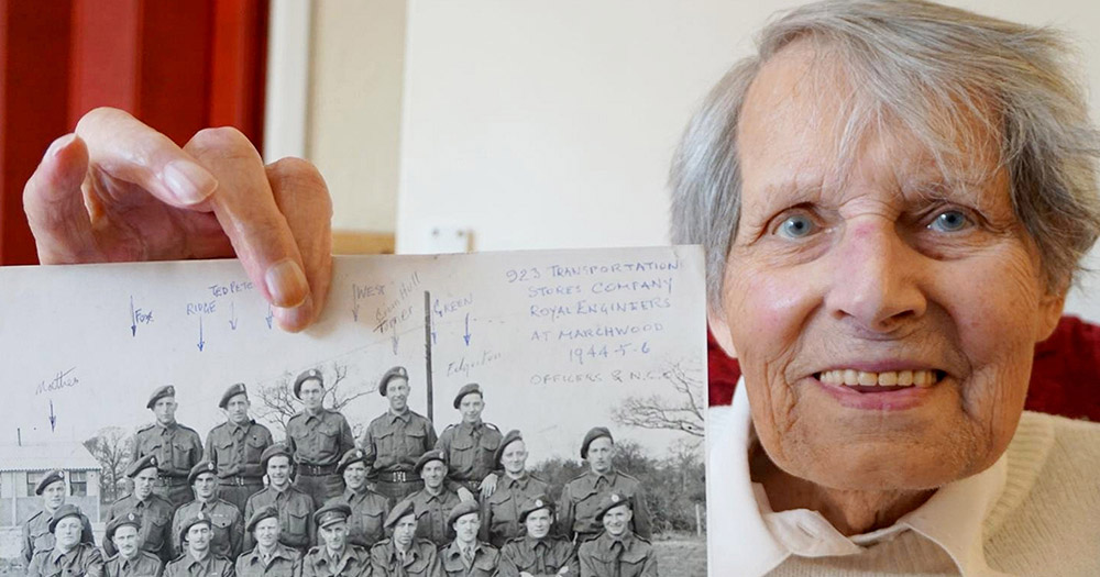 Louise Jennings holding a photo of her time during World War 2 with other soldiers.