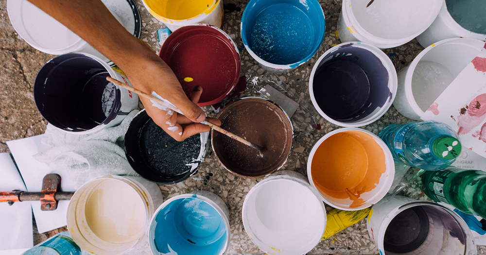 Hand holding paintbrush dipped in paint surrounded by other pots of paint