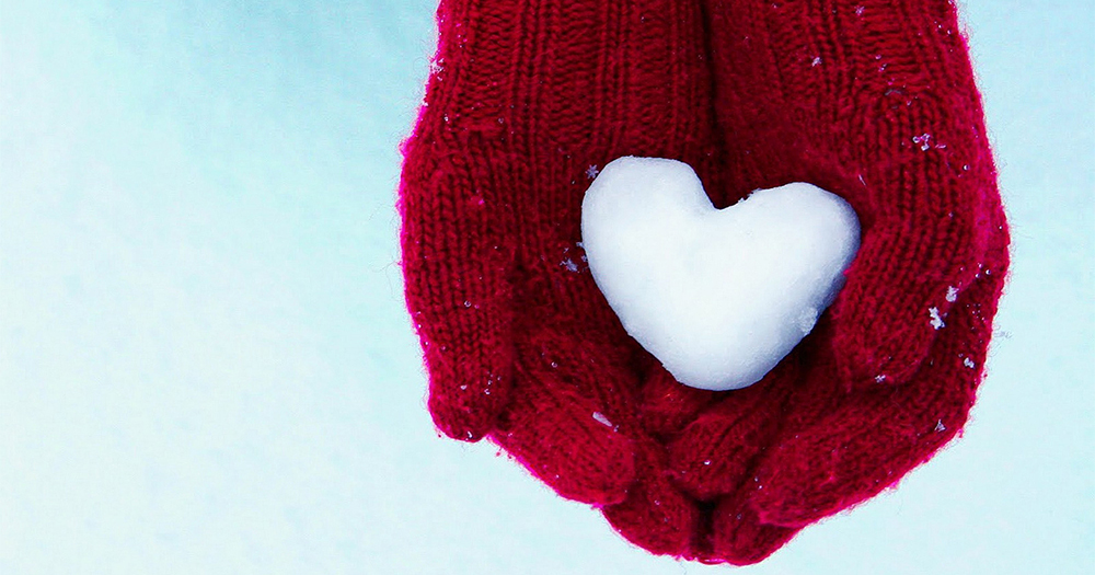 Ways to give back this Christmas: a pair of hands wearing red gloves holding heart-shaped snow