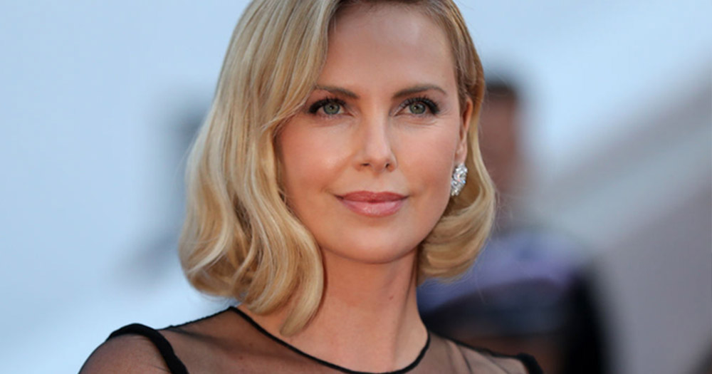 Charlize Theron smiling and looking off in the distance, wearing a black dress