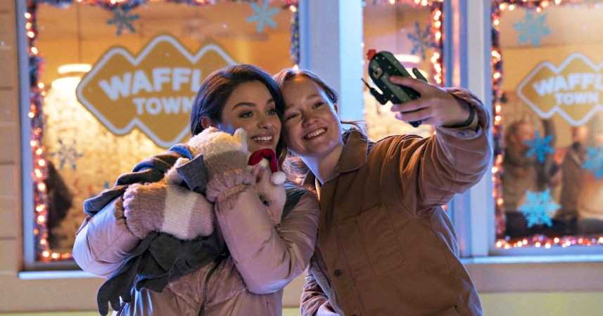 One of the Christmas queer movies : two young women taking a selfie while holding their pet wearing a Santa hat