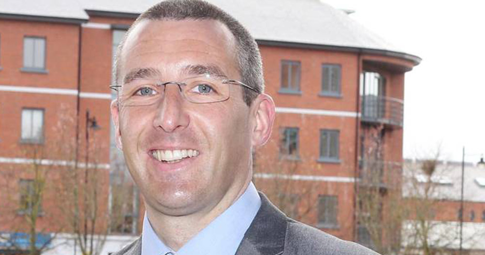 Openly gay councillor Andrew Muir smiling in front of orange brick flats, second out person elected to the Northern Ireland assembly
