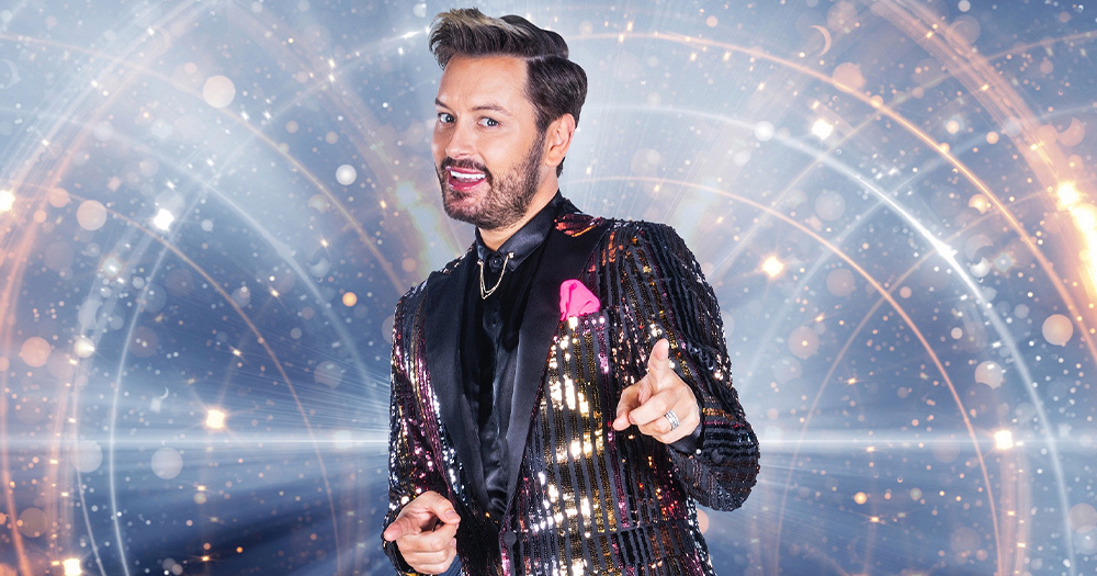 Brian Dowling, a man with dark hair wearing a sparkly suit, points at the camera, smiling