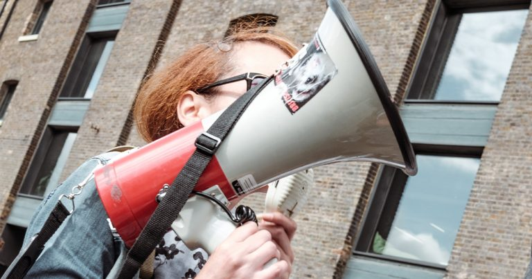 A woman holding a megaphone, it obscures her face
