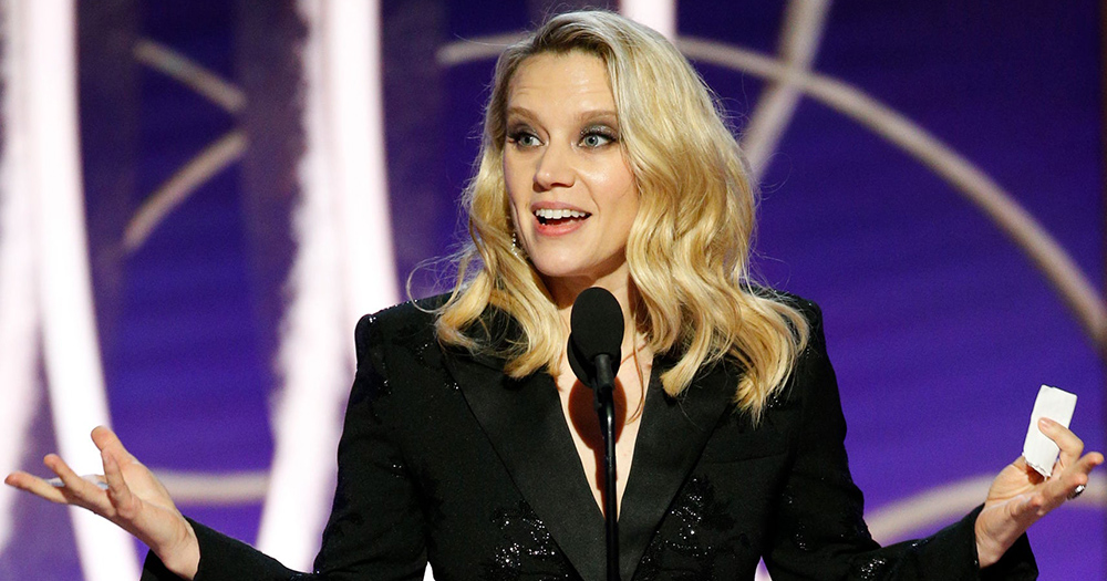 Kate McKinnon with long hair and a dress suit holds her hands wide speaking into a microphone on stage.