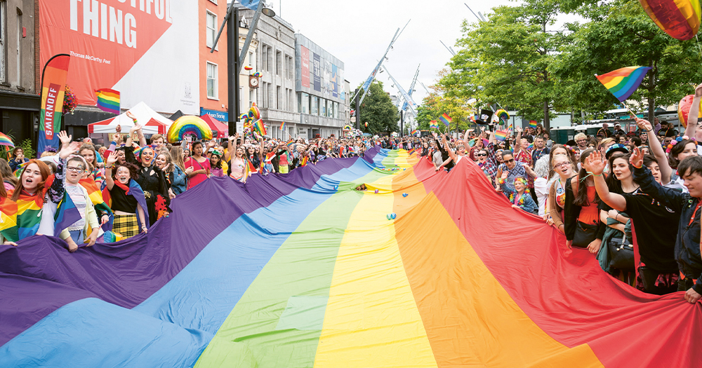 A huge crowd of people stretching a massive rainbow flag the length of a street
