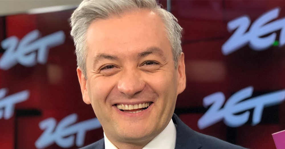 Robert Biedron, a man with grey hair wearing a suit, smiles hugely at the camera