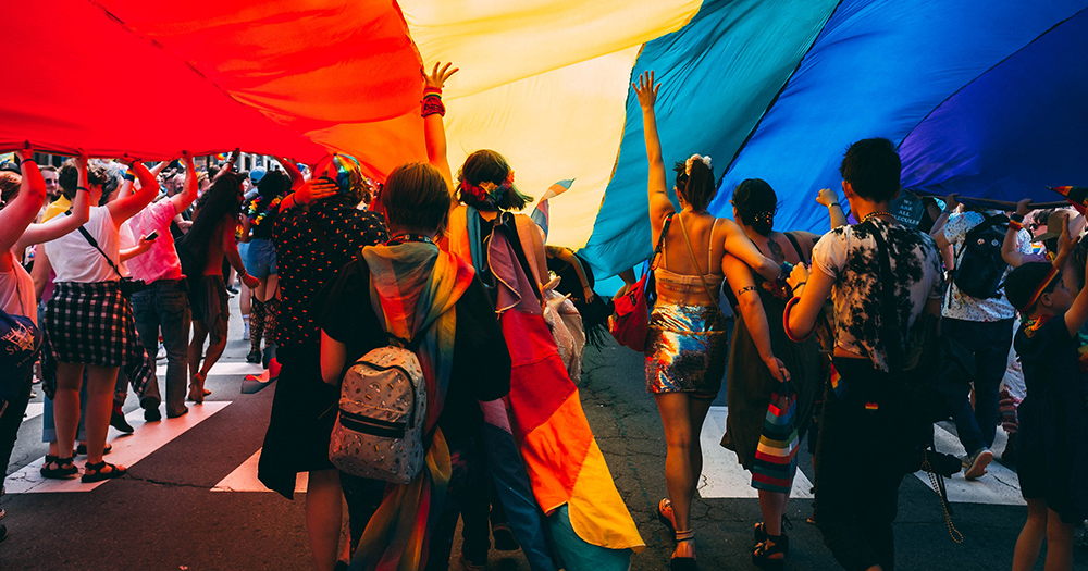 A group of people walking underneath a huge piece of fabric dyed rainbow colours