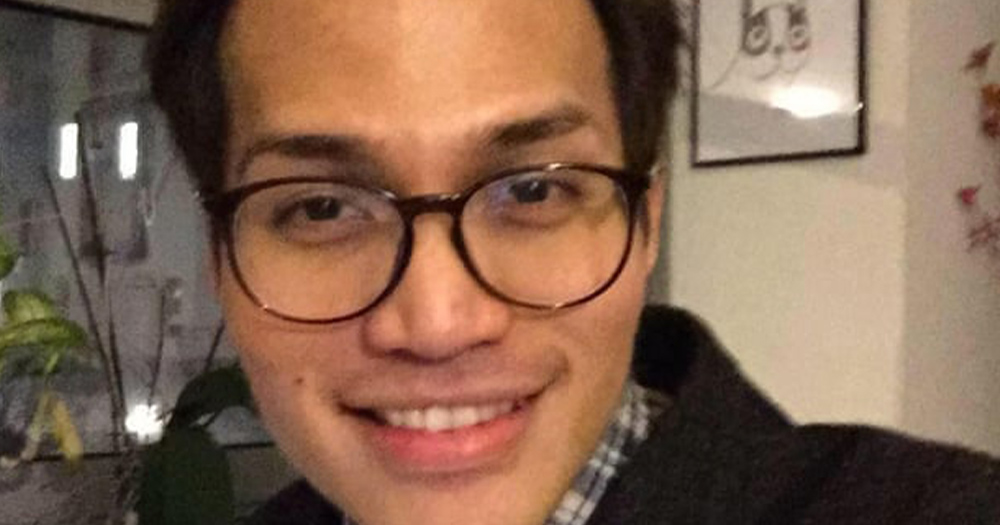 Reynhard Sinaga, an Indonesian man wearing glasses smiles at the camera