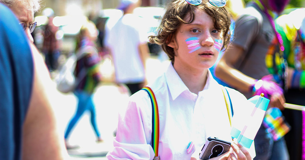 A young person with a trans flag in their hands and painted on their face stands in the street