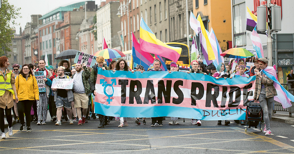 A huge rally of people holding a banner reading Trans Pride Dublin