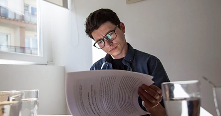A man in Kosovo wearing glasses sits at a table reading a file with sun streaming in the window