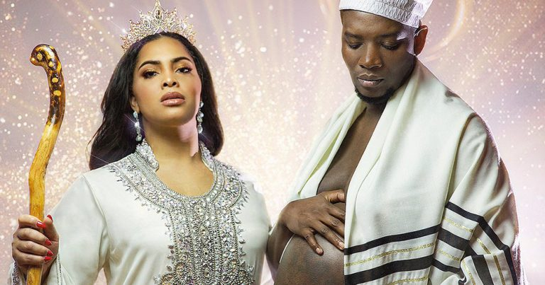 Trans masc person and wife posing in nativity style dress, showing off pregnancy.