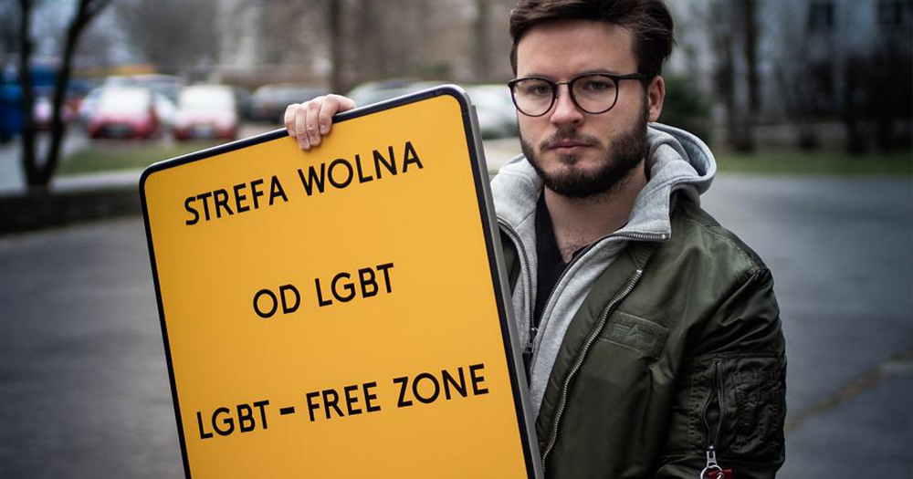 Activist, Bartosz Staszewski, holding his fake 'LGBT free zone' sign, he has taken photos of queer people in Poland.