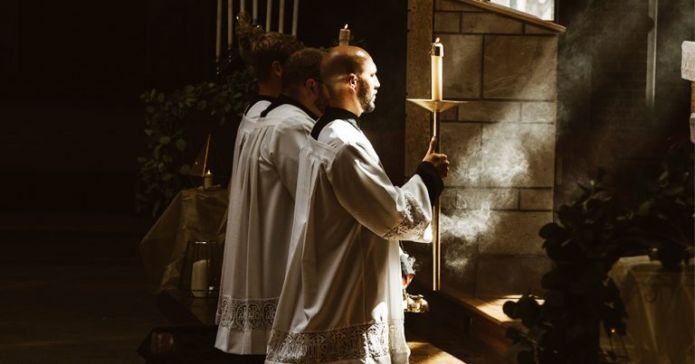 Three priests kneel in a shaft of sunlight, holding candles
