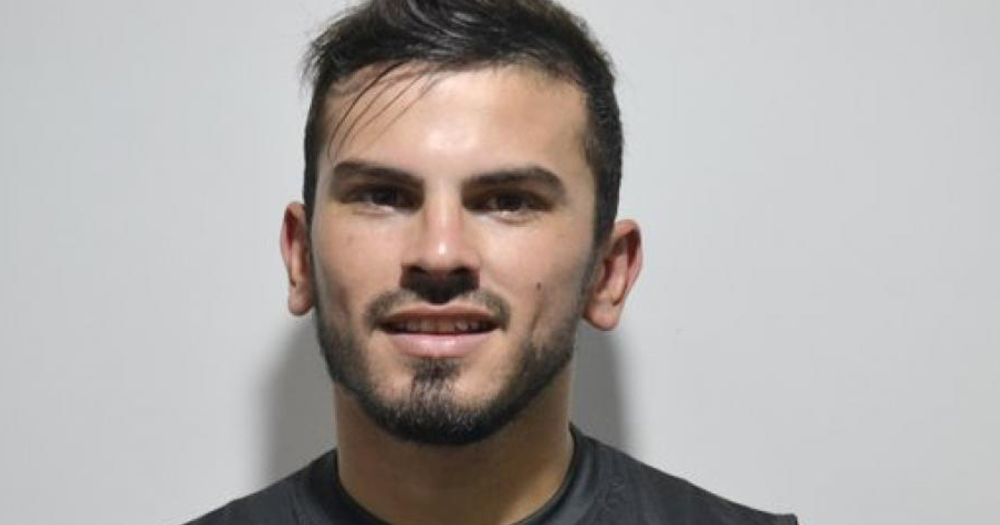 Nicolás Fernández was the first openly gay professional football players in Argentina, he is smiling in front of a grey wall