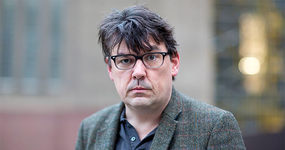 A man with messy hair and a dishevelled suit wearing glasses